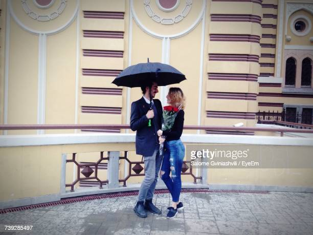 Full Length Of Romantic Couple In Umbrella Standing Against Building