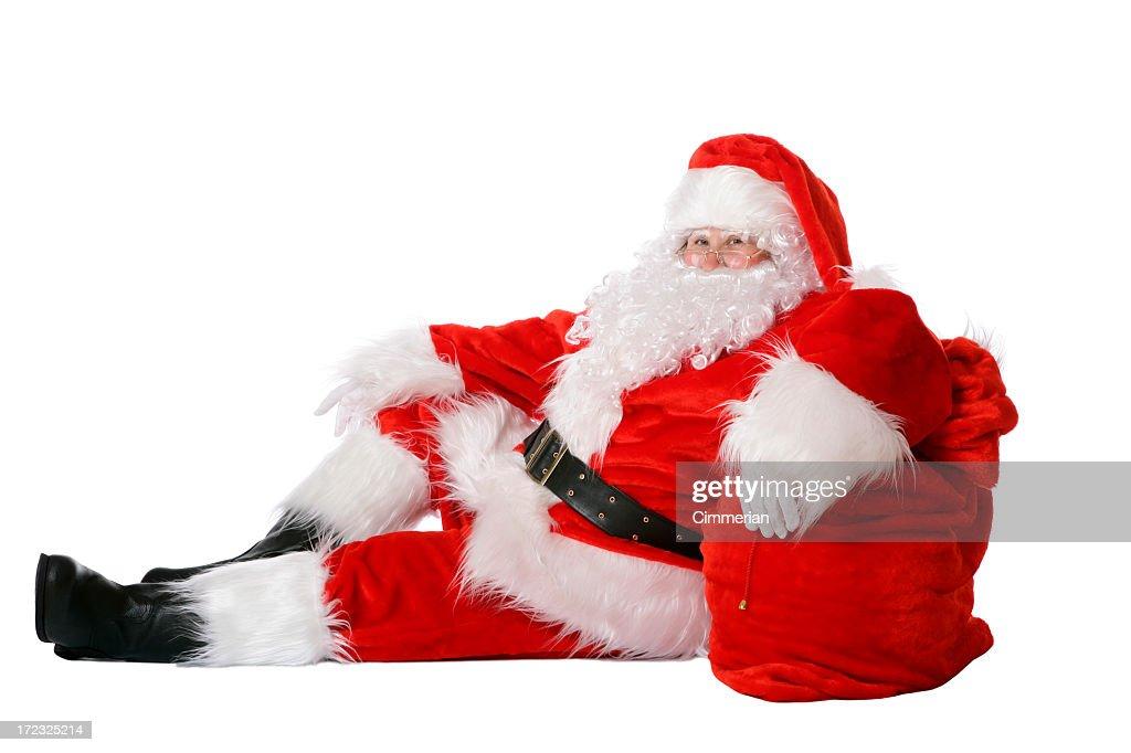Full Length Of Santa Relaxing Against His Sack Of Toys
