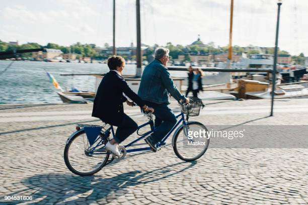 Full length of senior couple riding tandem bike on road in city during vacation