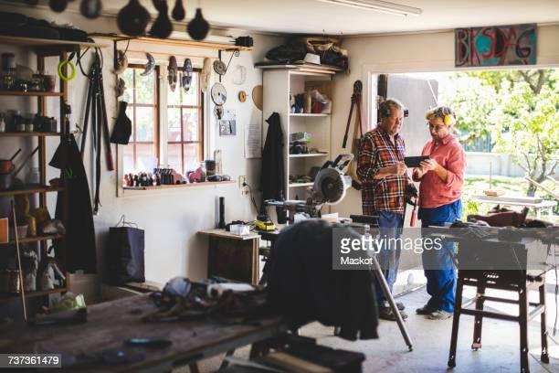 Full length of senior couple using digital tablet in workshop