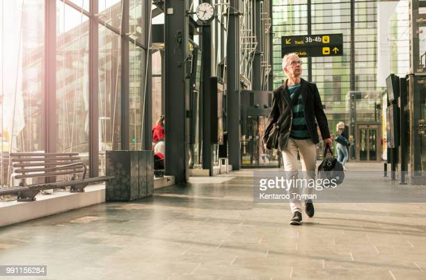 full length of senior male commuter walking with luggage at railroad station - station stock pictures, royalty-free photos & images
