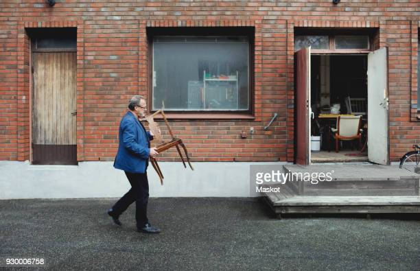 full length of senior man carrying wooden chair while walking by workshop - carrying imagens e fotografias de stock