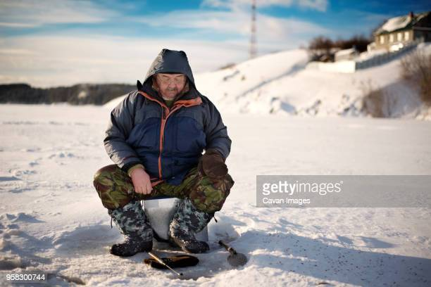 full length of senior man ice fishing in frozen lake - ice fishing stock pictures, royalty-free photos & images