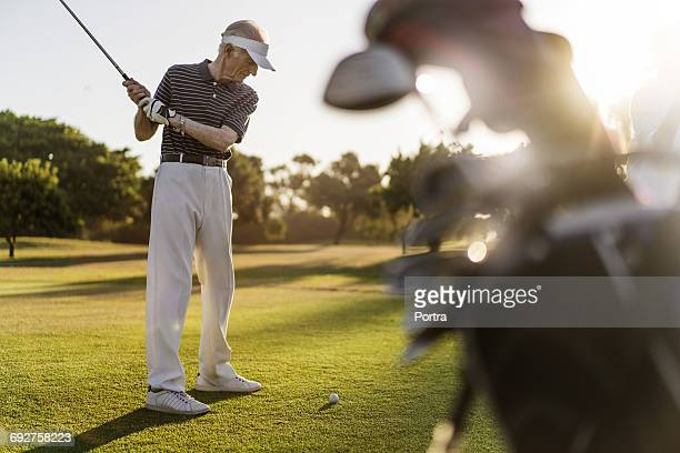 Full length of senior man playing on golf course