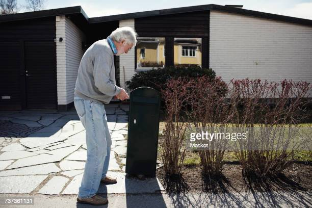 Full length of senior man standing by mailbox outside house during sunny day