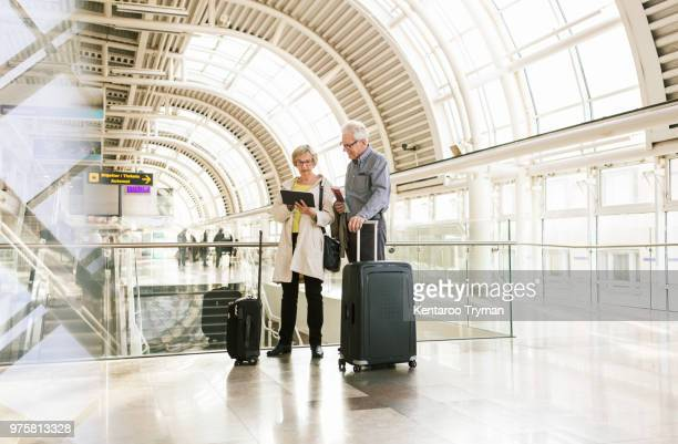 Full length of senior woman holding digital tablet by man standing with luggage at subway station