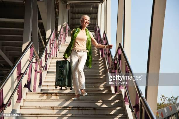full length of senior woman moving down stairs - só uma mulher idosa imagens e fotografias de stock
