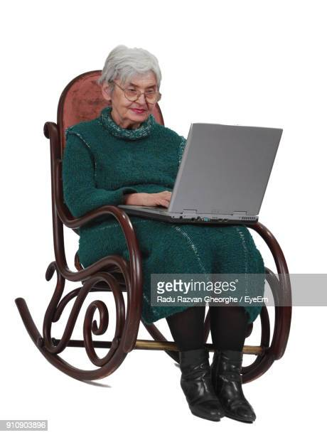 full length of senior woman using laptop while sitting on chair against white background - rocking chair stock photos and pictures