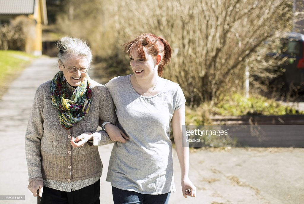 Full length of senior woman with female home caregiver walking arm in arm on street : Stock Photo