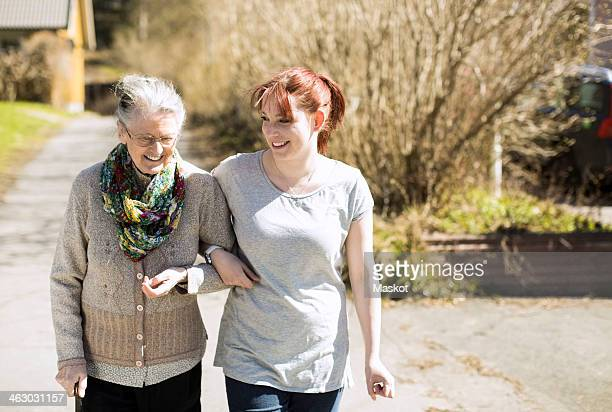 Full length of senior woman with female home caregiver walking arm in arm on street