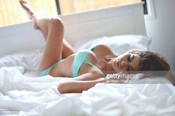 full length of sensuous female model in turquoise lingerie lying on bed - lingerie stock photos and pictures