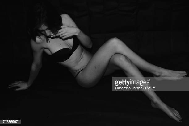 Full Length Of Sensuous Woman Sitting Against Black Background