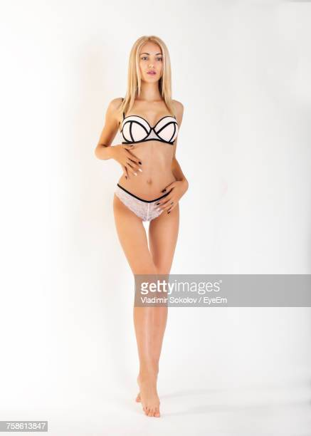 full length of sensuous young woman in bra and panty against white background - full frontal woman fotografías e imágenes de stock
