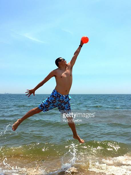 Full Length Of Shirtless Man Jumping While Catching Ball Over Shore During Summer