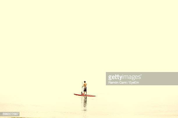 Full Length Of Shirtless Man Paddleboarding Over Sea Against Clear Sky