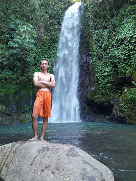 Full Length Of Shirtless Man Standing On Rock In Forest