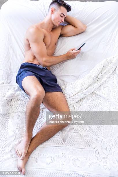 full length of shirtless man using phone while lying on bed - halbbekleidet stock-fotos und bilder