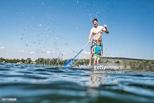 Full Length Of Shirtless Man With Son Paddleboarding On River Against Sky