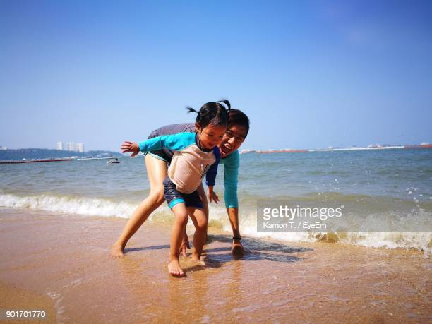 Full Length Of Siblings Playing At Beach Against Clear Sky
