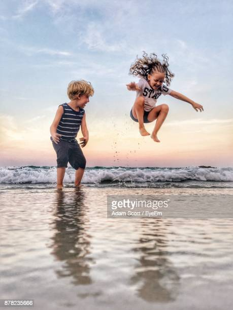 full length of siblings playing on shore at beach against sky - adam scott kids stock pictures, royalty-free photos & images