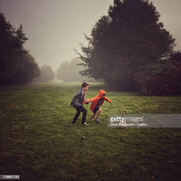 full length of siblings playing soccer on grassy field during foggy weather - football bulge stock photos and pictures