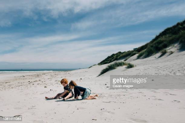 full length of siblings playing with sand at beach against cloudy sky during sunny day - dunedin new zealand stock pictures, royalty-free photos & images