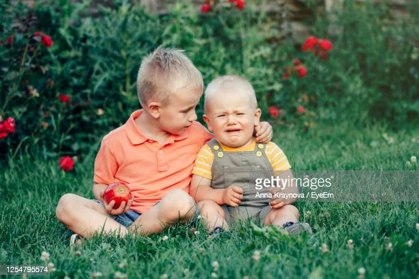 full length of siblings sitting on grass - compassionate eye stock pictures, royalty-free photos & images