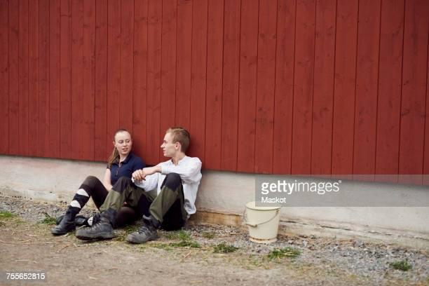 Full length of siblings talking while sitting against barn