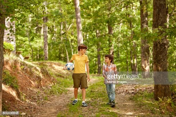 full length of siblings walking on pathway - 6 7 anni foto e immagini stock
