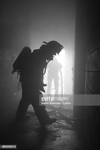full length of silhouette firefighters abandoned building - capacete de bombeiro - fotografias e filmes do acervo