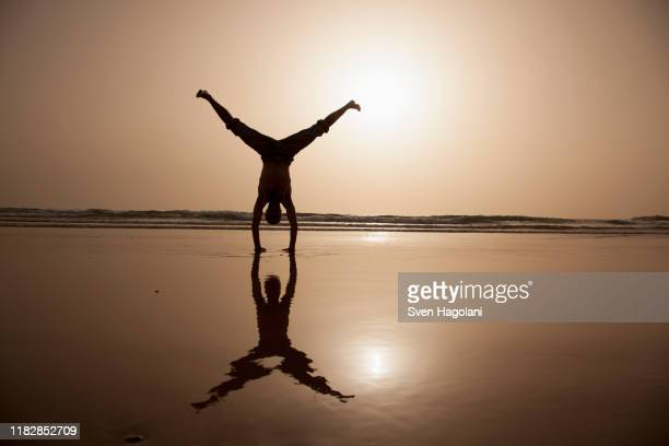 full length of silhouette man performing handstand at beach - legs apart stock pictures, royalty-free photos & images
