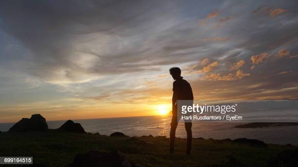 full length of silhouette man standing at beach against sky during sunset - harli stock pictures, royalty-free photos & images