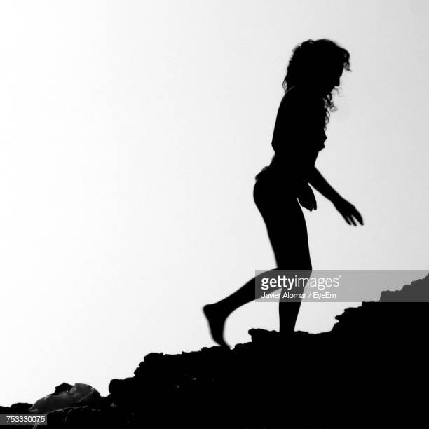 full length of silhouette woman walking on rock against white background - rock object photos et images de collection