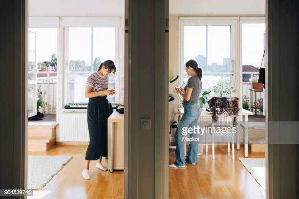 Full length of sisters using mobile phone while standing by wall at home