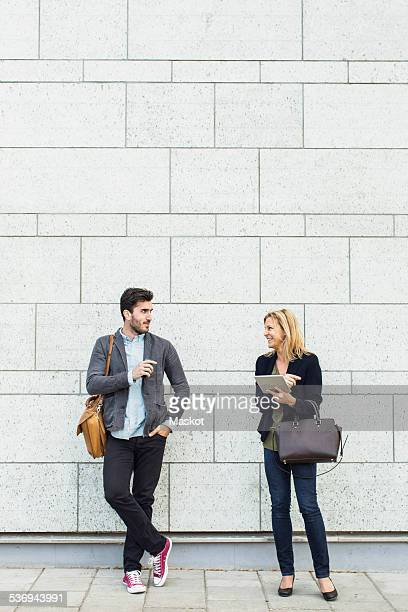 Full length of smiling business people discussing on sidewalk