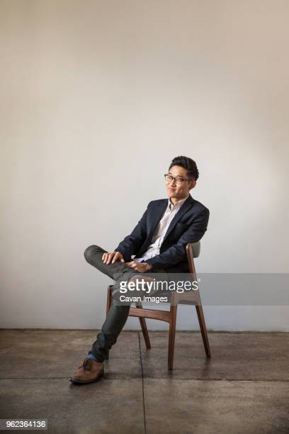 full length of smiling confident businessman sitting on chair against wall in office - smart casual stock pictures, royalty-free photos & images