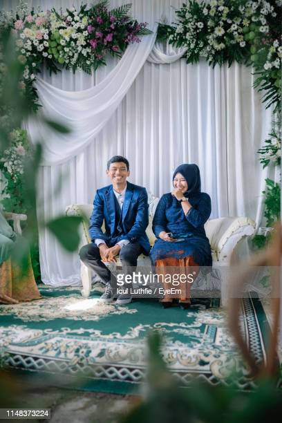 Full Length Of Smiling Couple Sitting On Sofa In Wedding Ceremony
