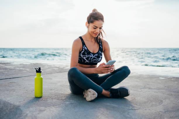 Full length of smiling female athlete using smart phone on promenade