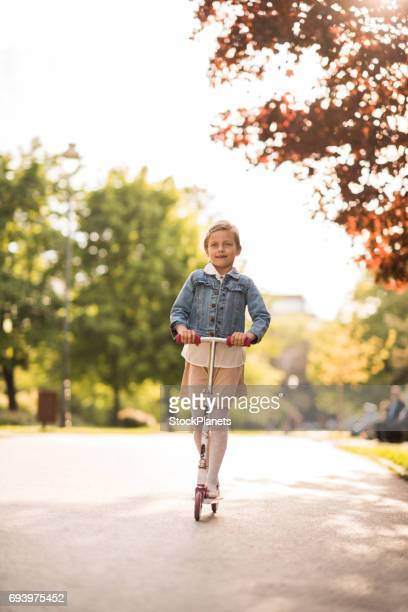 Gesamte Länge der lächelnde Mädchen Spaß auf Push Scooter.
