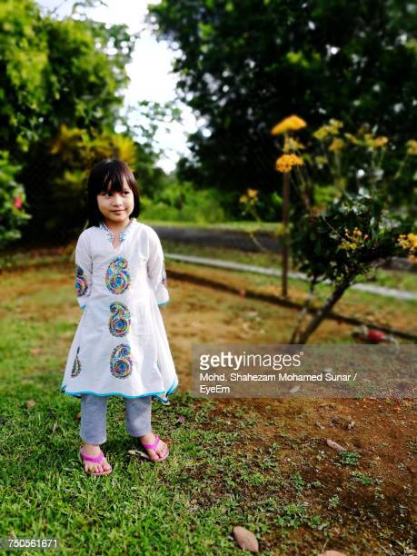 full length of smiling girl standing on field at park - malaysia beautiful girl stock photos and pictures