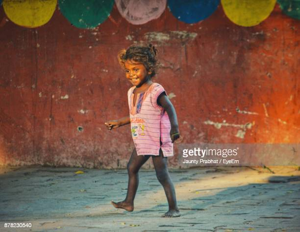 full length of smiling girl walking on footpath - children only stock pictures, royalty-free photos & images