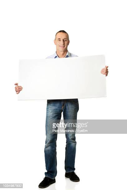 full length of smiling man holding blank placard while standing against white background - person holding up sign stock pictures, royalty-free photos & images