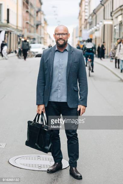 full length of smiling mature businessman standing on city street - blazer photos et images de collection