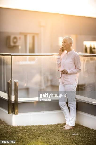 full length of smiling senior woman talking on smart phone on a terrace. - só uma mulher idosa imagens e fotografias de stock