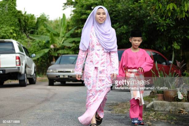Full Length Of Smiling Siblings Walking On Road