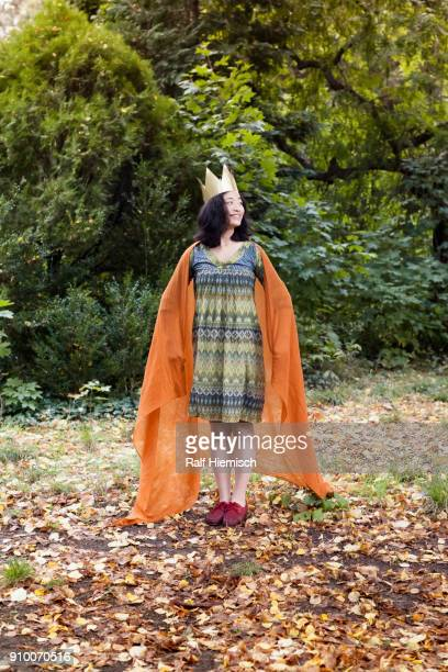 Full length of smiling woman wearing crown standing against trees at park during autumn