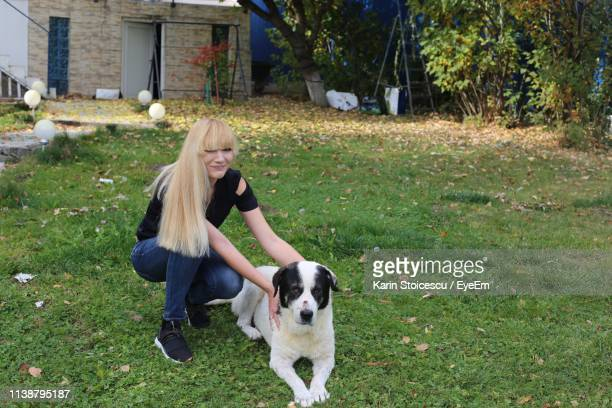 Full Length Of Smiling Woman With Dog At Yard