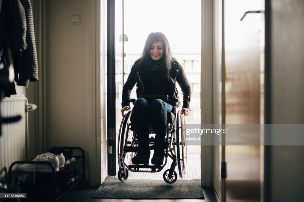 Full length of smiling young disabled woman entering home : Stock Photo