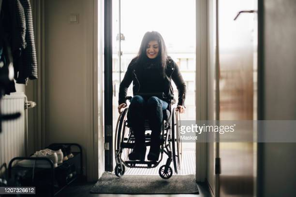 full length of smiling young disabled woman entering home - disability stock pictures, royalty-free photos & images