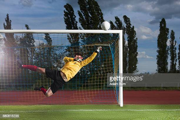full length of soccer goalkeeper diving to block ball - shooting at goal photos et images de collection